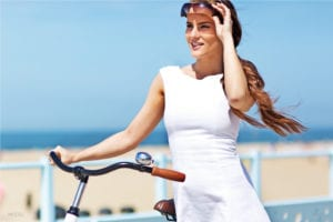 Female Model Contemplating Breast Augmentation Surgery Standing Next To Bike